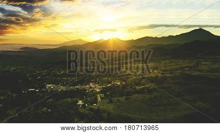 Aerial view of tea plantation with a village and sunrise landscape. Shot at Subang highlands West Java - Indonesia