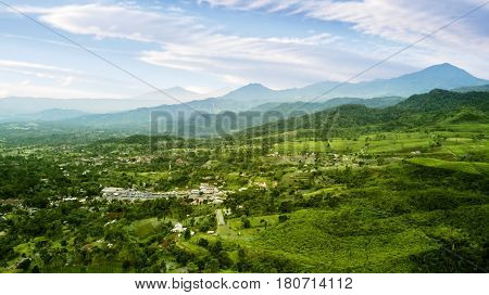 Aerial view of tea plantation highlands with village and mountain view. Shot at Subang highlands Indonesia