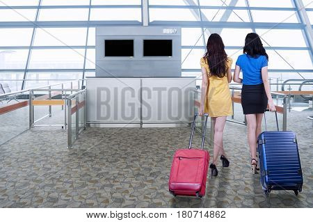 Rear view of two young women walking in the airport while carrying luggage