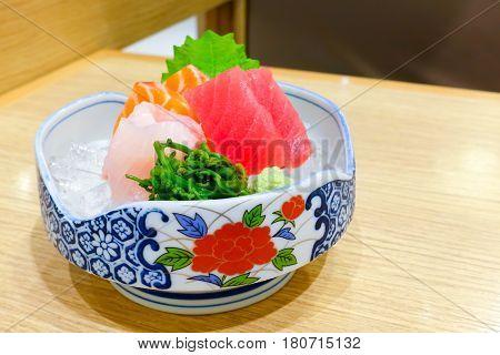 Mixed sashimi; hirame salmon and tuna sashimi served with wasabi on the flowers tile bowl