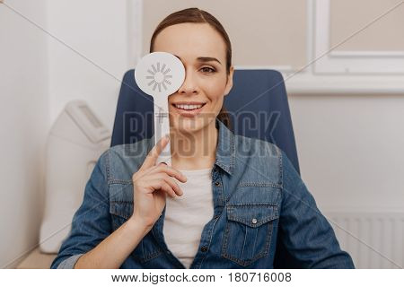 Eyesight test. Positive happy nice woman closing her right eye and smiling while having the eyesight test
