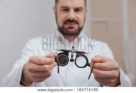 Diagnostic equipment. Selective focus of eye examination spectacles being in hands of a confident experienced ophthalmologist
