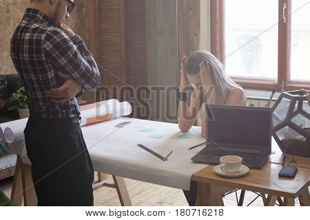 Deadline in architecture workshop. Boring architect woman keep head by two hands while working on blueprints and outlays sitting at table in modern studio. Team of talented workers correct mistake