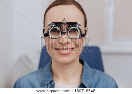Positive mood. Pleasant joyful nice woman smiling and looking at you while wearing special eye test spectacles