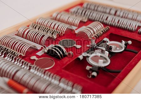 Collection of lenses. Close up of an open box with ophthalmic equipment lying in it while being ready to be used for eye examination