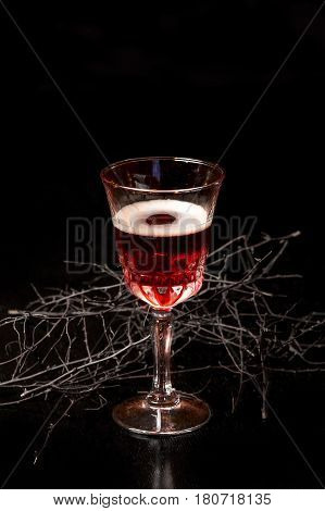 The tall glass of bloody red cranberry liquor on the black table with magic decoration.