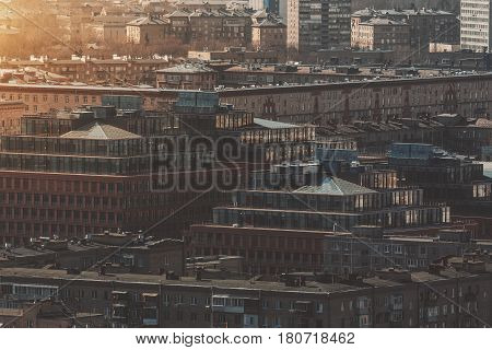 Close-up view from high point of residential district onsunny spring morning: multiple houses two buildings with pyramidal glass roofs multiple facades with balconies and windows Moscow Russia