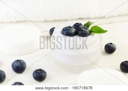 Skincare cream container with fresh indigo blueberries. White and blue tones. Holistic botanical beauty treatment product.