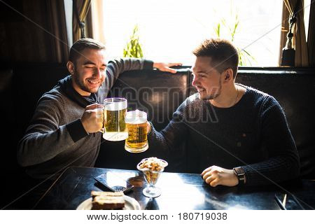 Two Young Man Sitting In Pub, Eating And Drinking Beer At Pub