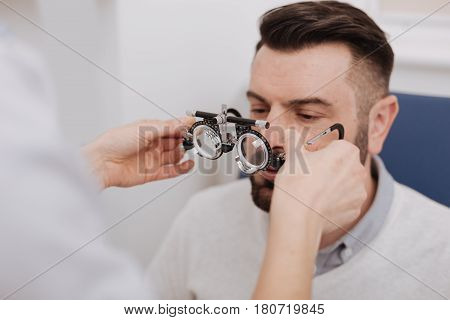 Special diagnostic optics. Professional experienced good looking ophthalmologist holding eye examination glasses and helping her patient to wear them while testing his eyes
