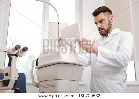 I do not understand. Serious confused male ophthalmologist standing in front of the monitor and looking at it while seeing the discrepancy in the results
