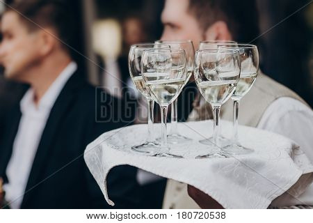 Champagne And Wine Glasses On Tray At Luxury Wedding Reception At Restaurant.  Waiter Serving Drinks