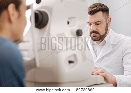 Focused on the job. Serious professional male optometrist using eye testing equipment and examining the vision of his patient while concentrating on his work