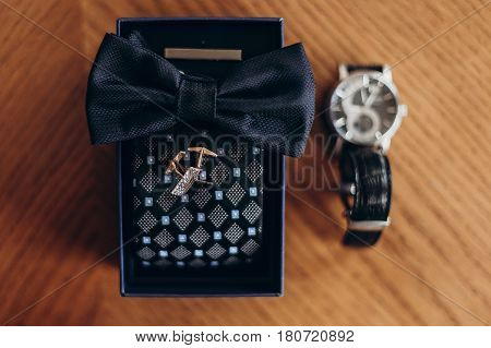 Golden Cuff Links Bow Tie And Watch On Wooden Table. Luxury Groom Set. Wedding Preparation In Mornin