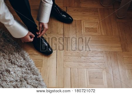 Groom Tying Shoes, Getting Ready In The Morning On Wooden Floor. Hotel Room. Preparation For Wedding