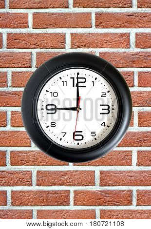 Big round clock with a black rim showing nine o'clock hangs on red brick wall front view close up