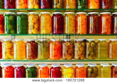 Various jars with Home Canning Fruits and Vegetables jam on glass shelves