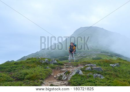 Man traveler with big backpack goes the mountain trail through the fog. Difficult journey.