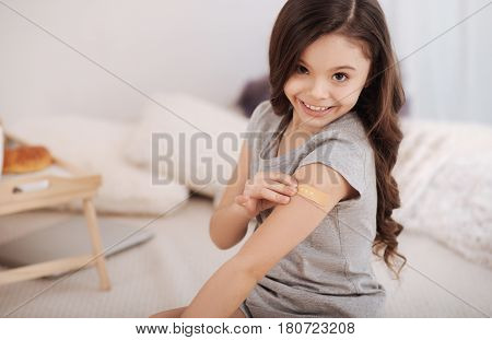 Allergy away. Positive beautiful little girl sitting in the white colored room and putting band aid on her arm while enjoying weekend