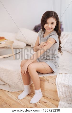 Nothing scary. Positive peaceful little kid sitting in the white colored room and putting band aid on her arm while enjoying medicine