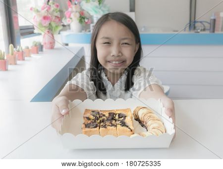 Asian Kid Holds Banana Toast On The White Table.