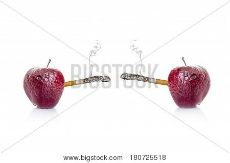 rotten apple with a cigarette, the concept of harm of smoking on a white background