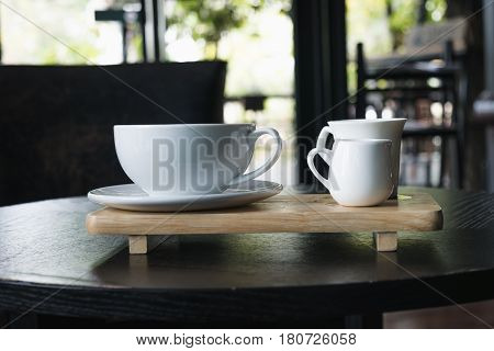 White Cup Of Coffee On Wooden Table In The Coffee Shop.