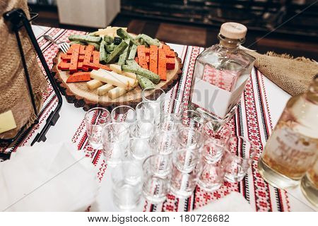 Cheese On Wooden Plate And Empty Glasses At Bottles Of Vodka On Table At Luxury Wedding Reception. M