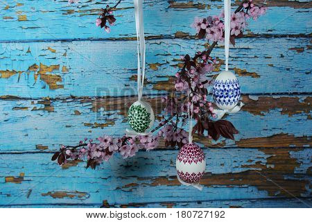 Painted Easter eggs with cherry branch and wood background