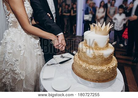Golden Wedding Cake. Bride And Groom Cutting Together Their Gold Cake With Crowns And Money At Luxur