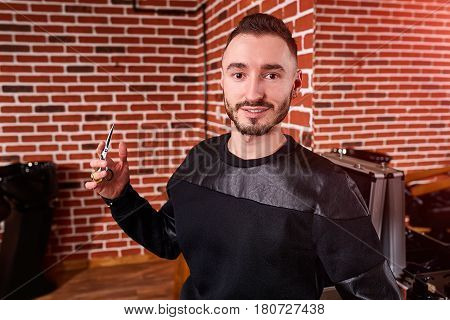 Handsome bearded hairdresser in stylish black wear is holding a scissors while standing at the barbershop against brick wall. Interior of the barbershop. Mirror and barber tools. Horizontal photo. Professionalism and craftsmanship.
