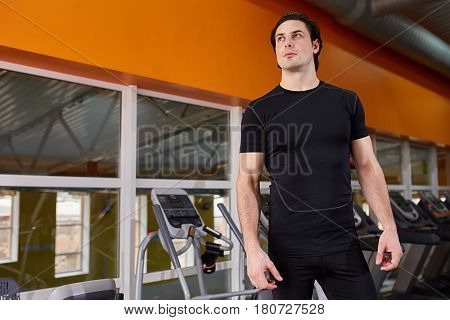 Lifestyle portrait of handsome muscular man in the black t-shirt and shorts standing in the sport gym against simulator. Horizontal photo. Beautiful athlete man. Healthy lifestyle.