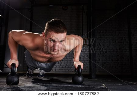Sportsman doing push-ups exercise with kettlebell in a crossfit workout against brick wall. Close-up portrait of the athletic man. Sportsman in the sporty shorts. Concept of the healthy lifestyle.