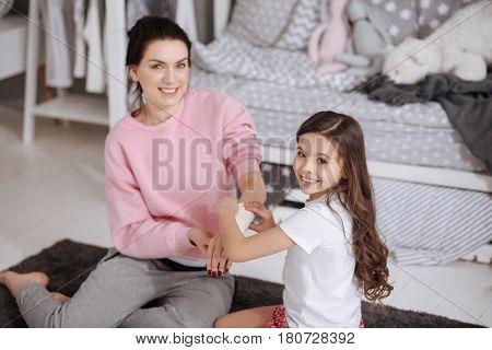 Happy motherhood. Cute charming beautiful girl sitting in the night nursery and taking care of her mother while using elastic roller and bandaging