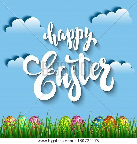 Multi colored easter eggs in grass against the blue sky and clouds with the handwriting lettering Happy Easter