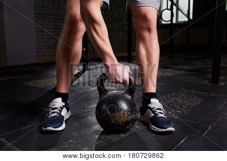 Close-up photo of man's legs and arm while holding kettlebell on the gym floor against dark background. Sporty man in the sneackers. Muscles of the young athletic man. Concept of the crossfit activity. Healthy lifestyle.
