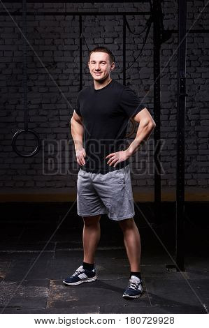 Photo of a young crossfit sportsman in sportwear while standing against brick wall. Sportsman in the t-shirt, shorts and sneackers. Portrait of athletic man. Vertical photo. Healthy lifestyle.