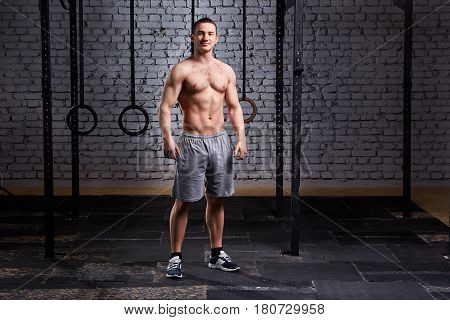 Photo of a young muscular crossfit sportsman while standing against brick wall. Sportsman in the shorts and sneackers. Portrait of athletic man. Horizontal photo. Healthy lifestyle.
