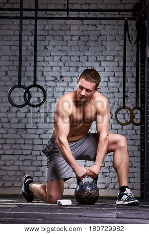 Vertical photo of young athletic man while holding kettlebell on the gym floor against brick wall. Sporty man in the sneackers and shorts. Muscles of the young athletic man. Concept of the crossfit activity. Healthy lifestyle.