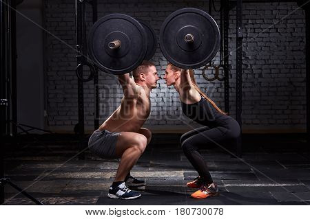 Crossfit lifting bar by woman and man in group workout against brick wall. Concept of crossfit activity in couple. Man and woman in the sportwear. Healthy lifestyle. Opposite each other.