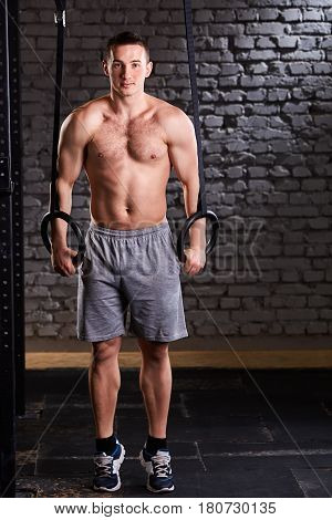 Sportsman doing pull ups with gymnastic rings for strength and crossfit exercise against brick wall. Athletic man in the shorts and sneackers. Muscular man. Power and energy. Healthy lifestyle.