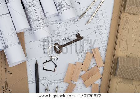 Workplace Of Architect - Key With Trinket In The Shape Of A House, Wooden Blocks, Construction Drawi