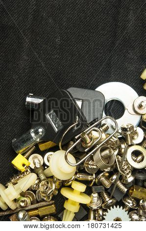 techno backgrounds - various bolts, screws, washers, nuts and other computer small fasteners on black fabric