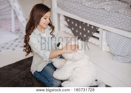 Having compassion on my toy. Smiling positive little child sitting in the night nursery and enjoying being doctor while treating and hugging fluffy bear
