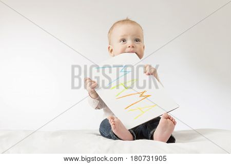 Cute baby boy with poster. Concept for postcard to Mothers day. Copy space. Colorful sign Mama.