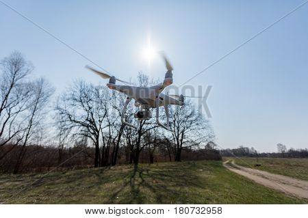 Copter soars from the ground to the sky against a background of green grass on the field. A drone with a high-resolution camera.