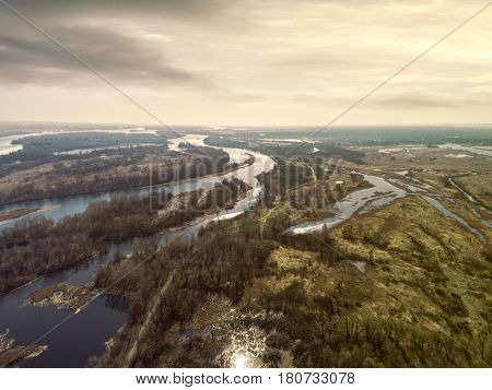 Early spring landscape from above. Aerial view. Outdoor. Green field with river and backwater skyline.