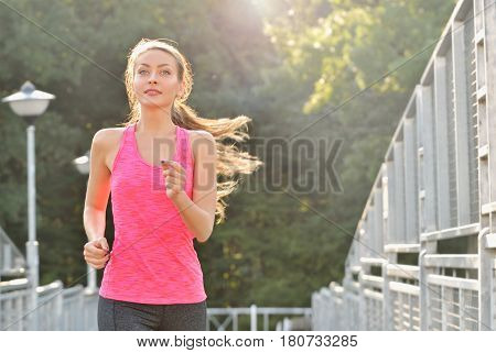 Woman running on bridge. Woman runner jogging on urban road training for marathon. Fit girl fitness athlete model exercising outdoor
