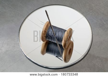Thread reel and needle on a round mirror