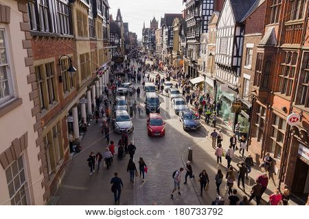 Chester England UK - March 25 2017: Shoppers and tourists making their way through Eastgate Street in the city centre with its mix of beautiful Tudor and neo-classical style buildings